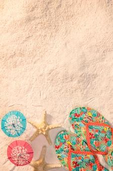 Bunte sandalen mit seestern am strand