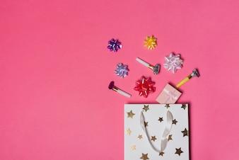 Bunte Satinschleife; Geschenkbox und Parteigebläse über der Papiertüte auf rosa Hintergrund