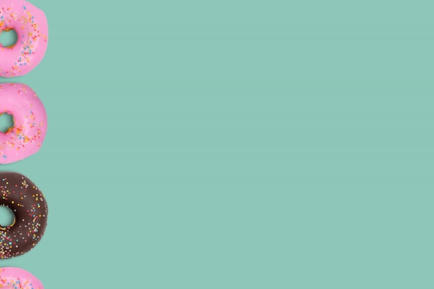 Bunte schaumgummiringe auf cyan-blauer weicher pastellfarbe.