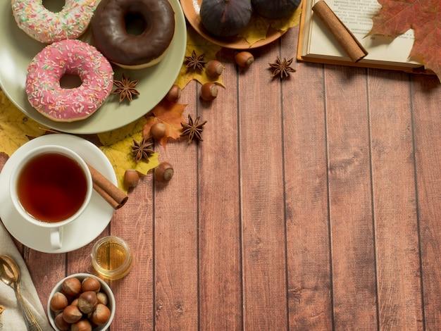 Bunte schaumgummiringe auf plattenherbst und einer tasse tee auf rustikaler holzoberfläche