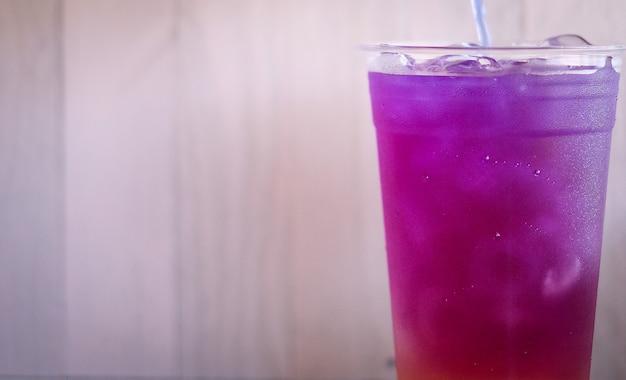 Bunte schicht des rosa und lila kräutertees. schmetterling erbsen tee kaltes getränk zur erfrischung.