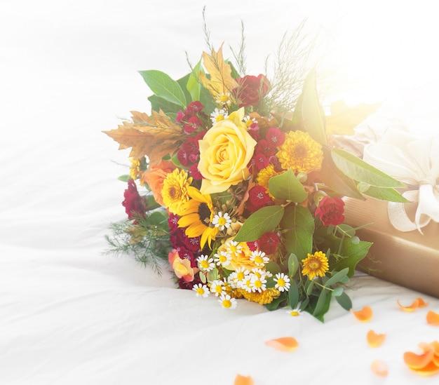 Bunte schöne frühling oder sommer blumenstrauß auf dem bett mit goldenen geschenk-box, urlaub oder überraschung konzept