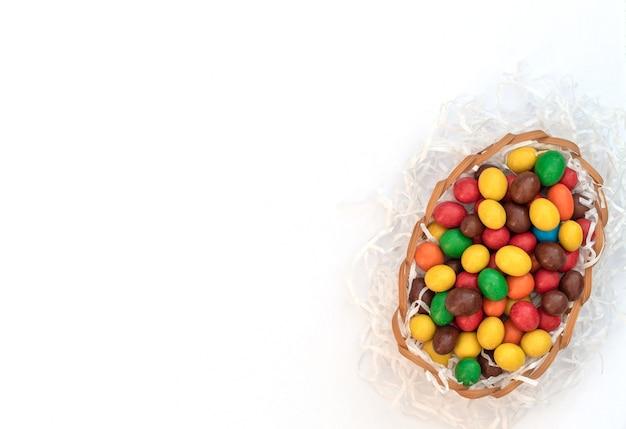 Bunte schokoladen-ostereier im eierkorb mit weißem papier wie ein nest