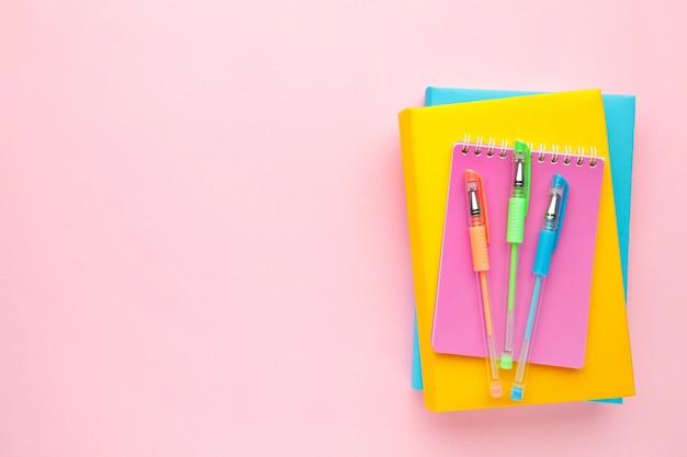 Bunte schulbücher mit stift auf rosa hintergrund