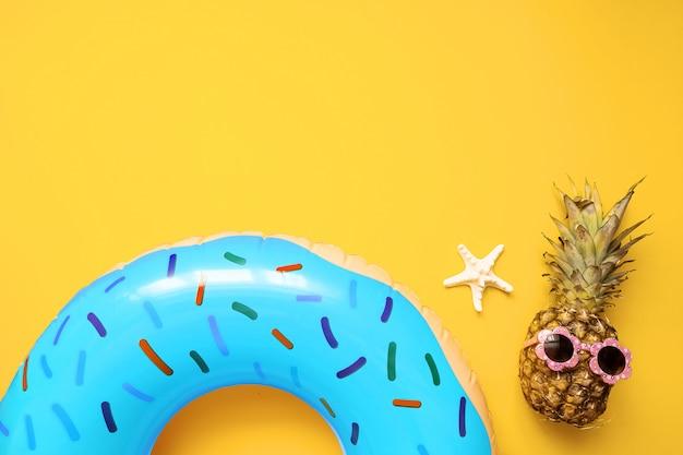 Bunte sommerflachlage mit blauem aufblasbarem kreisdonut, lustige ananas in der sonnenbrille