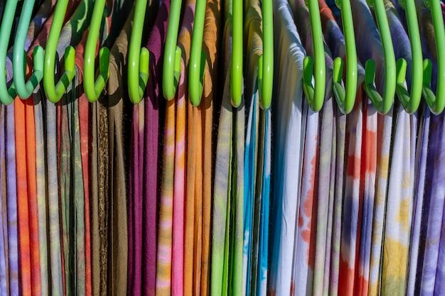 Bunte sommerkleidung auf kleiderbügeln zum verkauf auf dem lokalen straßenmarkt in thailand, nahaufnahme