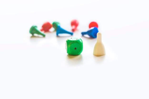 Bunte spielfiguren und plastikchips mit würfeln