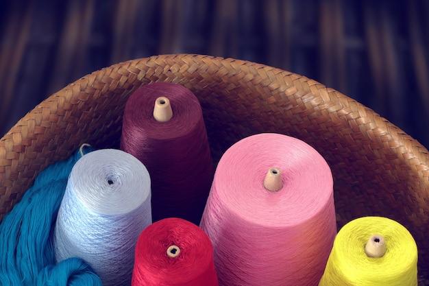 Bunte spulen des threads in einem weidenkorb. vintage-ton