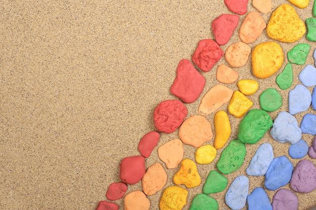 Bunte steine auf dem sand mit kopierraum ausgelegt
