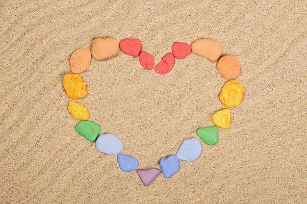 Bunte steine in form eines herzens auf dem sand
