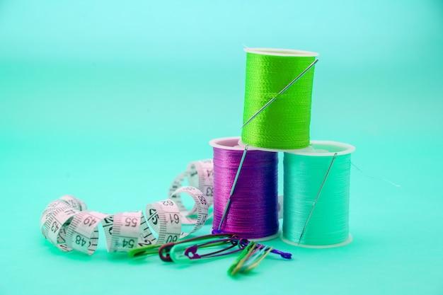 Bunte stickgarne, nadeln und zentimeterband an blauer wand