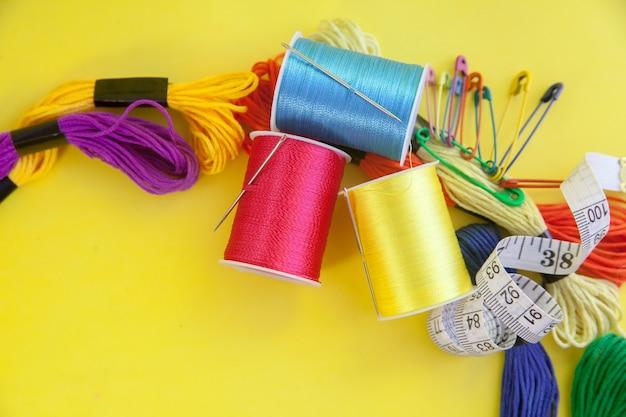 Bunte stickgarne, nadeln und zentimeterband an gelber wand
