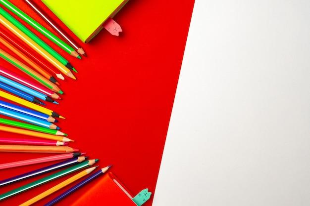 Bunte stifte und notizblöcke auf papier draufsicht, kopierraum