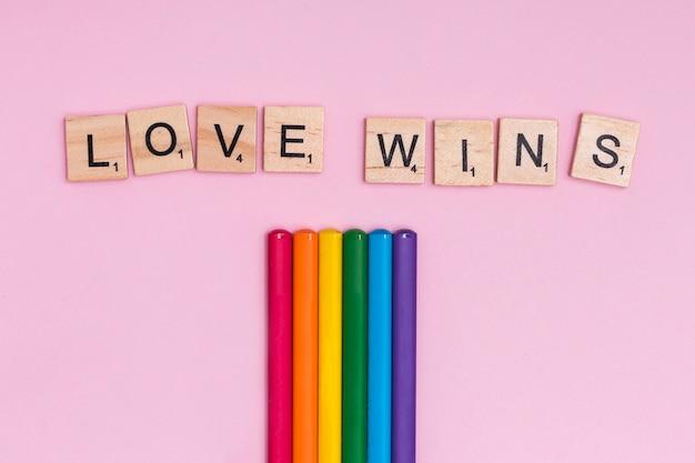 Bunte stöcke des regenbogens und love wins-zeichen