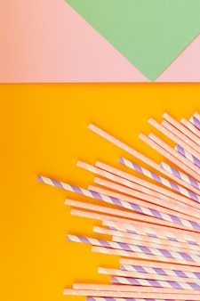 Bunte strohhalme aus papier für sommercocktails auf heller pastellwand mit kopierraum. umweltfreundliche wiederverwendbare strohhalme. papierstroh zum trinken von kaffee oder tee