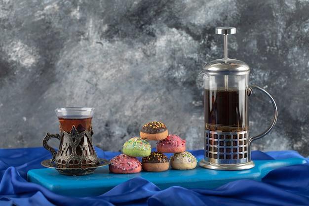 Bunte süße donuts mit einer tasse tee.