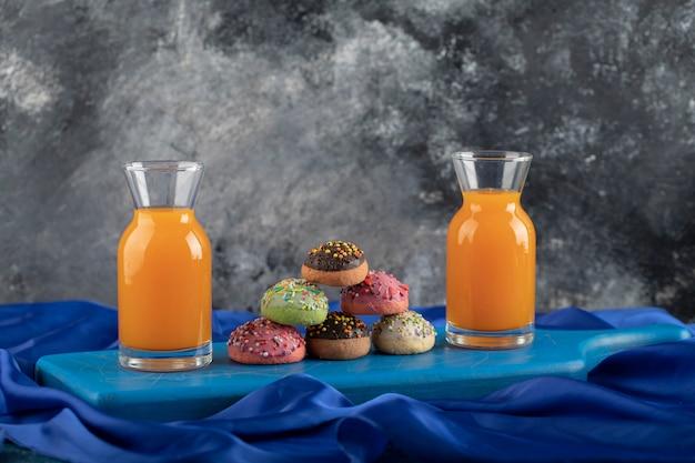 Bunte süße donuts mit gläsern saft und einer tasse tee.