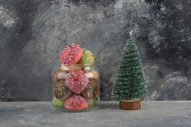 Bunte süße donuts mit weihnachtsbaumspielzeug.