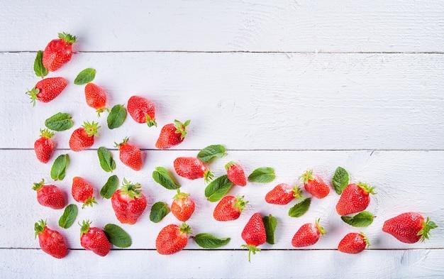 Bunte süße fruchtmischung von erdbeer- und grünen minzblättern auf weißem holztisch des jahrgangs. heller fruchthintergrund.