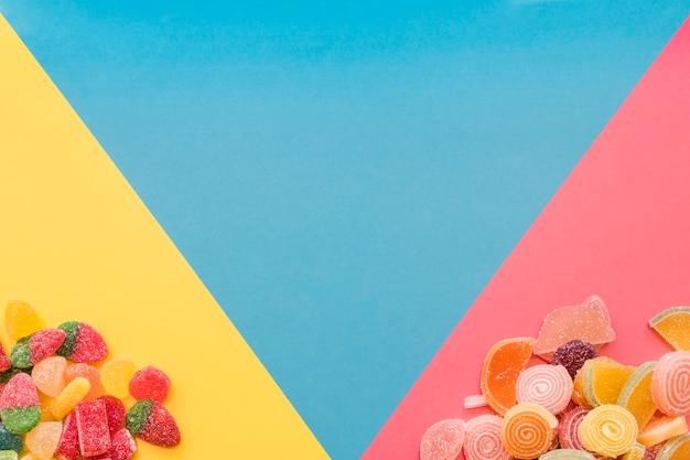 Bunte süße geleesüßigkeiten auf dem gelben und rosa dreieckigen hintergrund