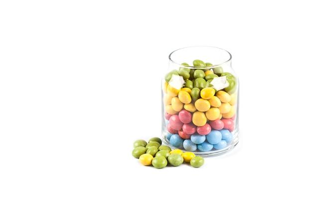 Bunte süße süßigkeiten im glasgefäß lokalisiert auf weiß