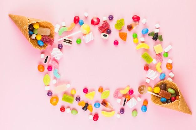 Bunte süße süßigkeiten mit zwei eiscreme-waffelkegel auf rosa oberfläche