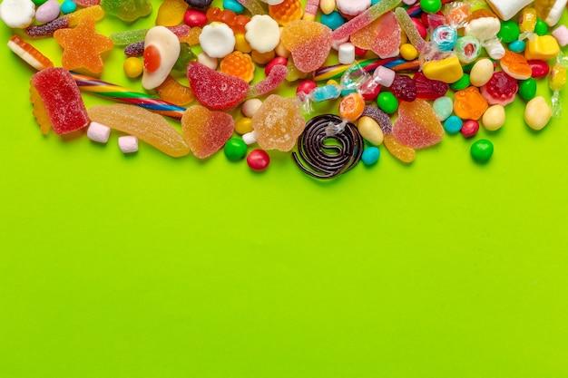 Bunte süßigkeiten auf grünem hintergrund