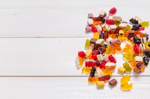 Bunte süßigkeiten auf hölzernem hintergrund