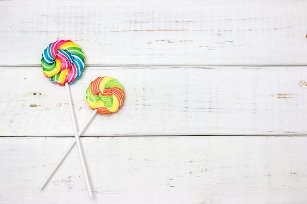 Bunte süßigkeiten auf holztischhintergrund. draufsicht mit kopienraum