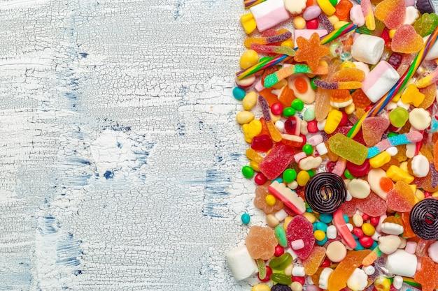 Bunte süßigkeiten auf holztischhintergrund.