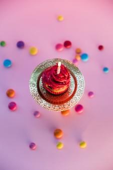 Bunte süßigkeiten breiteten sich über dem hellen kleinen kuchen auf rosa hintergrund aus