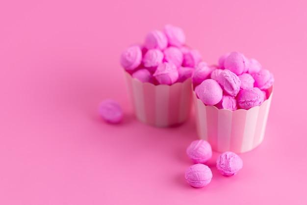 Bunte süßigkeiten der vorderansicht auf rosa, süßer zuckerfarbe der süßigkeit