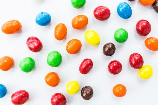 Bunte süßigkeiten, die auf weißem hintergrund liegen