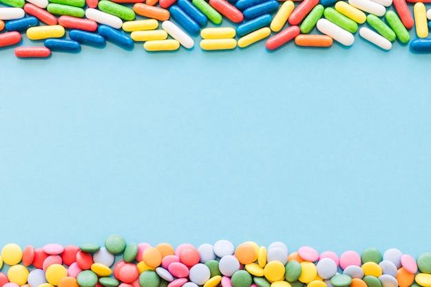 Bunte süßigkeiten, die die oberen und unteren grenzen auf blauem hintergrund bilden