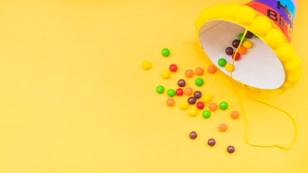 Bunte süßigkeiten, die parteishut auf gelbem hintergrund überlaufen