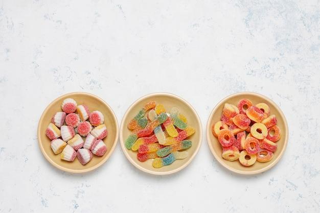 Bunte süßigkeiten, gelee, eibisch auf heller oberfläche. draufsicht mit kopienraum