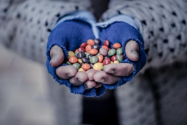 Bunte süßigkeiten. nahaufnahme einer handvoll bunter süßigkeiten, die ihnen gezeigt werden