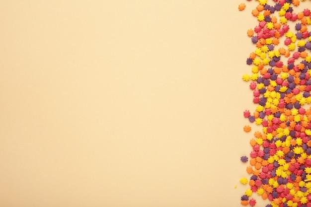Bunte süßigkeiten streut auf beigem hintergrund