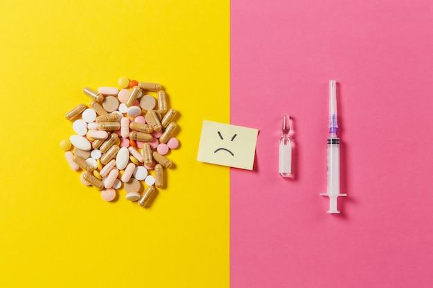 Bunte tabletten der medikamente, pillen, die abstrakt auf gelbem rosa hintergrund angeordnet sind