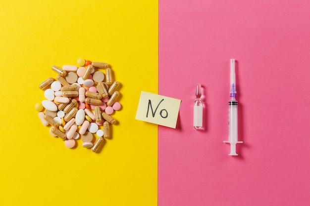 Bunte tabletten der medikation, pillen arrangierten abstrakt auf gelbem rosa hintergrund. aspirin, ampulle, leere spritzennadel, papieraufkleberbogen textwort-nr. behandlung, wahl, gesundes lebensstilkonzept.