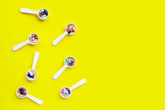 Bunte tabletten mit kapseln und pillen auf gelbem grund.