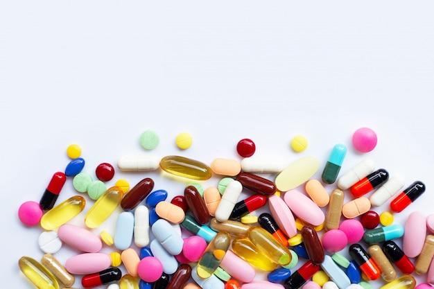Bunte tabletten mit kapseln und pillen auf weiß.