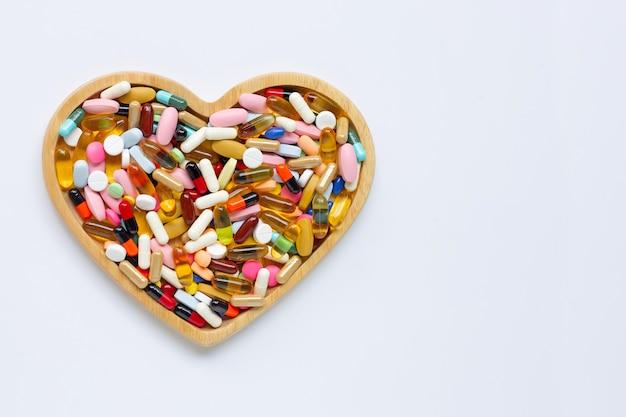 Bunte tabletten mit kapseln und pillen auf weißem hintergrund. hölzerne herzform platte.