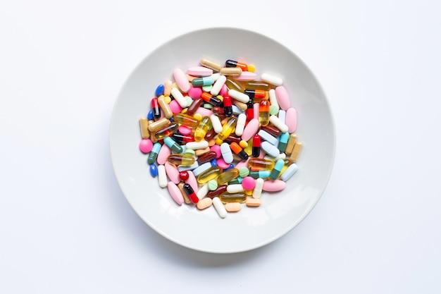Bunte tabletten mit kapseln und pillen auf weißem teller auf weiß
