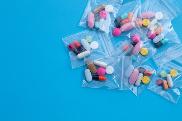 Bunte tabletten mit kapseln und pillen in medizintaschen an der blauen wand. draufsicht