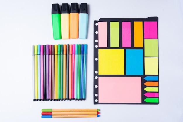 Bunte textmarker, stift, marker, klebriges papier und leeres papier zum arbeiten oder lernen