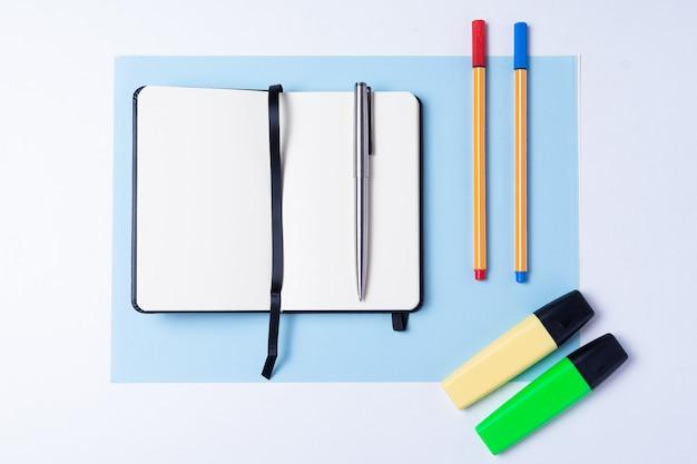 Bunte textmarker, stift, marker, notizbuch und leeres papier zum arbeiten oder lernen