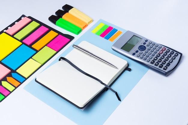 Bunte textmarker, stift, marker, taschenrechner, notizbuch und leeres papier zum arbeiten oder lernen