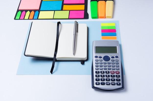 Bunte textmarker, stift, marker, taschenrechner und leeres papier zum arbeiten oder lernen