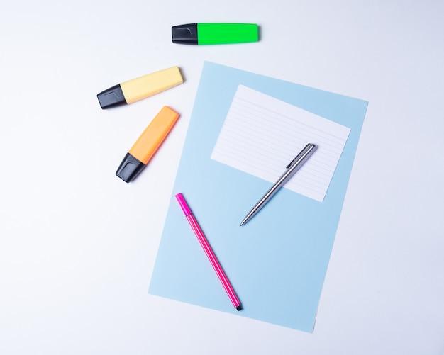 Bunte textmarker, stift, marker und leeres papier zum arbeiten oder lernen